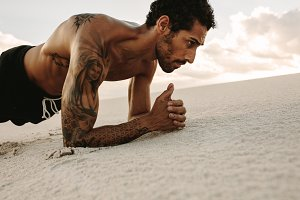 Athlete doing core workout on sand
