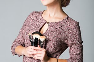 Beautiful makeup artist with brushes