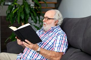 Retired man reading a book in his ho