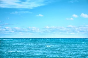 Sea water and blue sky with white cl