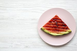 Grilled watermelon on a pink plate