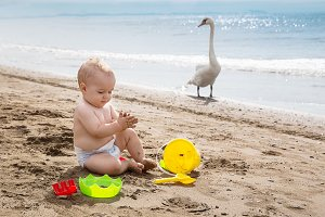 baby boy playing on the beach near a