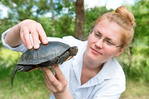 Pretty blond woman holding a turtle
