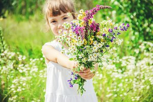Child with a bouquet of wildflowers.