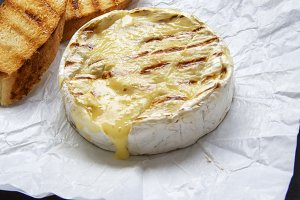 Grilled camembert cheese on black