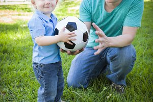 Young Boy and Dad Playing with Socce