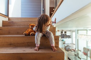 Little girl sitting on staircase