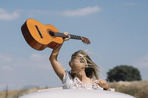Happy woman with the guitar by the r