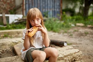 Poor homeless girl eating a piece of