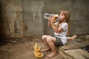 Poor homeless girl drinking water