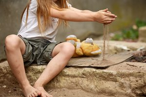 Orphan girl with bare feet in a