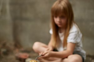 Homeless girl frying some bread in