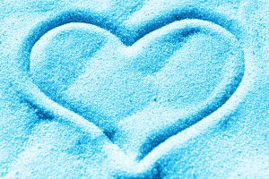 Blue heart on the sand