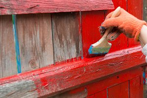 A painter painting wooden fence