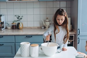 little girl cooks in the kitchen