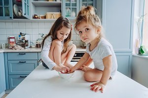 Two little girls in the kitchen sitt