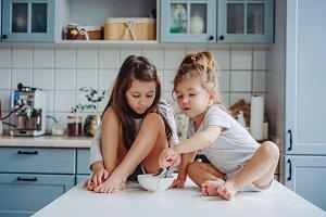 Two little girls in the kitchen sitt
