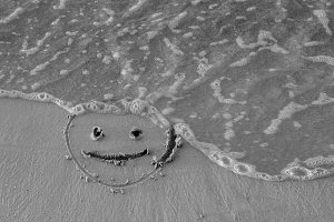 On the sand drawn a smiley face and