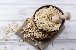 Oat flakes  in ceramic bowl and wood