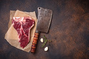 Raw T-bone steak with butchers knife