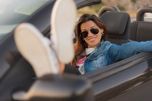 young woman enjoying her convertible
