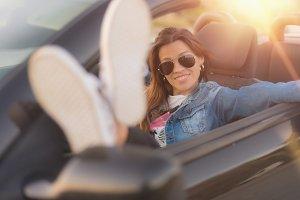 young woman enjoying her convertible