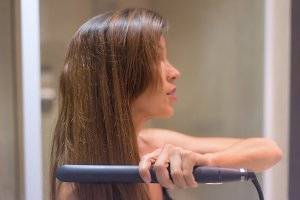 Beautiful Woman straightening hair.