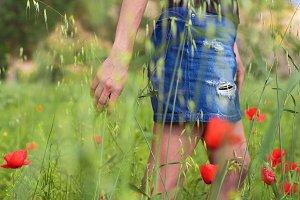 Woman enjoying a walk in a poppy fie