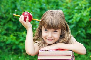 little girl student with a red apple