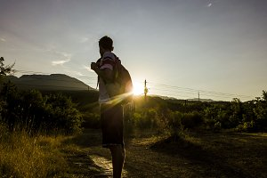 silhouette of young man with backpac