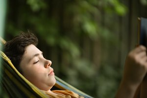teenager boy reading in hammock