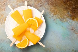 Orange popsicles with juice on a