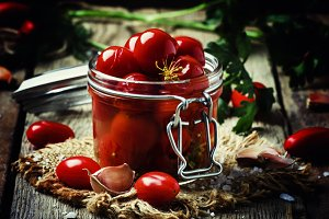 Pickled red cherry tomatoes in a gla