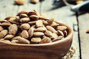 Raw almonds in bowls, old wooden bac