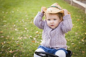 Toddler Wearing Cowboy Hat and Playi