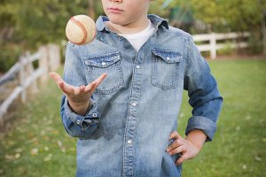 Handsome Young Boy Tossing Up Baseba