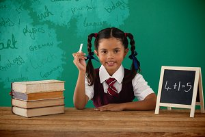 Schoolgirl calculating sums at desk