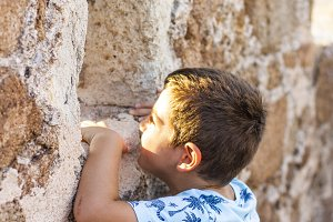 Little boy looking through the wall