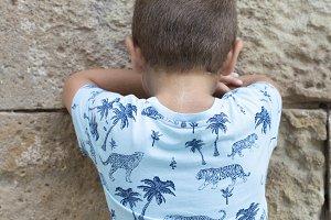 Little boy facing the wall outdoors
