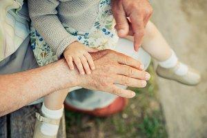 Baby girl touching hand of senior ma