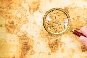 Old map and magnifying glass in a ha