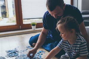 Father and daughter playing puzzle