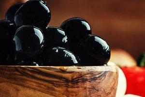 Black olives in a wooden bowl, selec