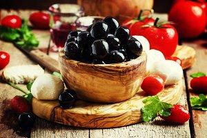 Black olives in a vintage wooden bow