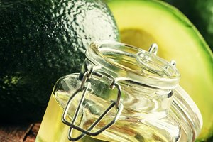 Cosmetic avocado oil in a glass jar,