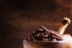 Raw pecan nuts in wooden bowl, rusti