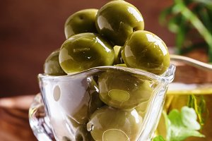 Green greek olives in glass bowl on