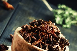 Anise stars in a wooden bowl, dark b