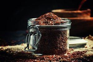 Crude red rice in a glass jar, black