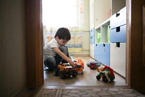 boy playing alone in room, lonely